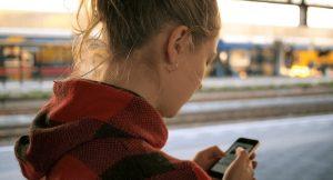 Visuele weergave van 5G in Nederland. Een vrouw gebruikt haar telefoon op een treinstation