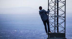 Visuele weergave van 5G straling. Een man staat op een zendmast en kijkt over de stad.