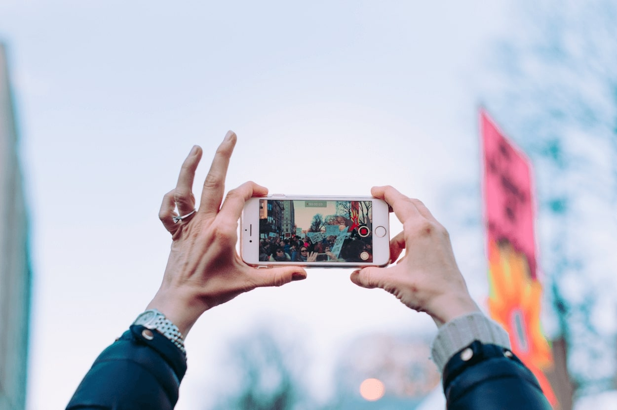Visuele weergave van een persoon die een foto maakt met een iPhone 5G